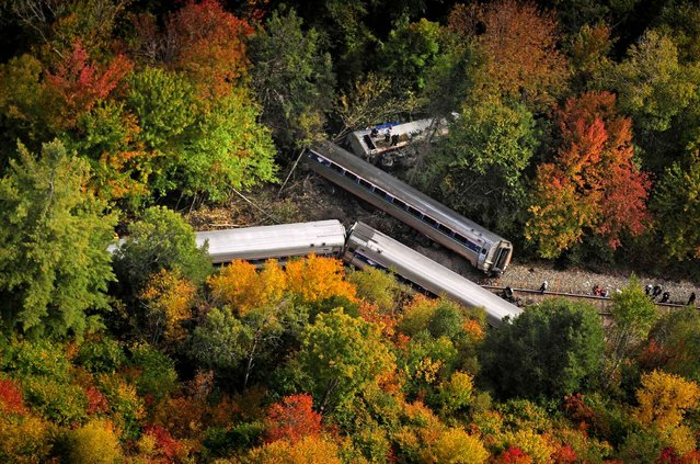 In this aerial photo railroad passenger cars from a derailed Amtrak passenger train are surrounded by foliage, Monday, October 5, 2015, in Northfield, Vt. The train, the Vermonter, was headed from Vermont to Washington, D.C., when it apparently struck rocks that were on the tracks. No life-threatening injuries were reported. (Photo by Stefan Hard/Barre-Montpelier Times Argus via AP Photo)