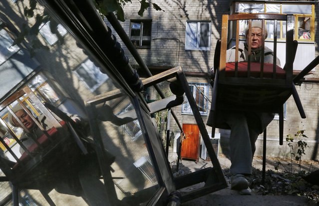 In this photo taken on Monday, October 27, 2014, a woman carries a chair as she moves her belonging from her damaged house after shelling not far from Donetsk airport in the town of Donetsk, eastern Ukraine. (Photo by Dmitry Lovetsky/AP Photo)
