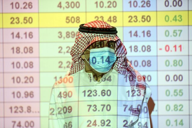A Saudi trader wears a mask as he monitors stock information at the Saudi stock market in Riyadh, Saudi Arabia on August 25, 2020. (Photo by Ahmed Yosri/Reuters)
