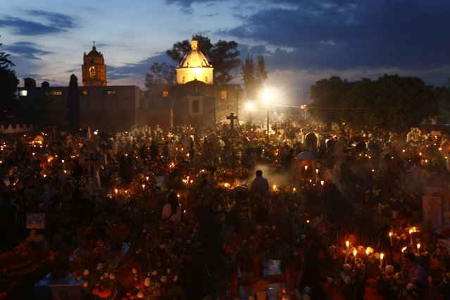 People stand near the graves of relatives at San Andres cemetery in Mixquic, November 2, 2014. On the Day of the Dead, Mexicans pay homage to their dead relatives by preparing meals and decorating their graves. The festival has its origins in a pre-Hispanic Aztec belief that the dead return to Earth one day each year to visit their loved ones. (Photo by Edgard Garrido/Reuters)