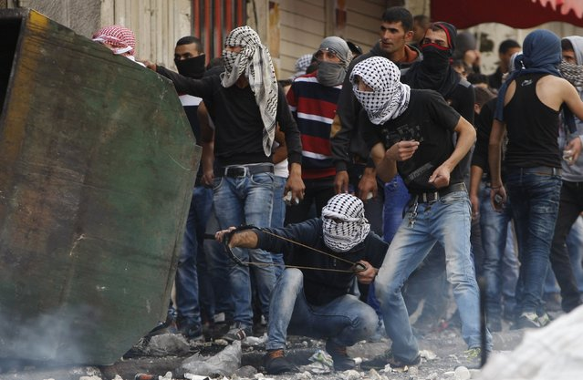 A masked Palestinian protester uses a slingshot to throw stones at Israeli troops as others take cover during clashes in the West Bank city of Hebron October 9, 2015. (Photo by Mussa Qawasma/Reuters)