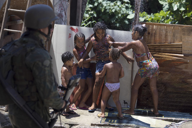 Children play in an outdoor shower as a soldier takes part in a surprise operation in the Manguinhos slum in Rio de Janeiro, Brazil, Thursday, January 18, 2018. (Photo by Leo Correa/AP Photo)