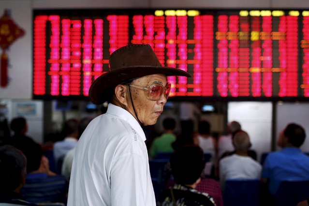 Tang Youyu, 73, wears a cowboy hat and sunglasses as he stands in front of an electronic board showingstock information at a brokerage house in Shanghai, China, July 13, 2015. Tang has lost over half of his money in the stock market but still hopes to win it back someday. He enjoys the atmosphere and the company of friends at the brokerage house. (Photo by Aly Song/Reuters)