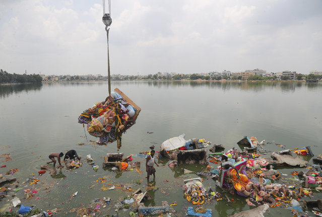 Indian workers remove idols of elephant-headed Hindu god Ganesha that were immersed earlier in  Saroornagar Lake on the final day of Ganesh Chaturthi festival in Hyderabad, India, Tuesday, September 1, 2020. The festival is a celebration of the birth of Ganesha, the Hindu god of wisdom, prosperity and good fortune. (Photo by Mahesh Kumar A./AP Photo)