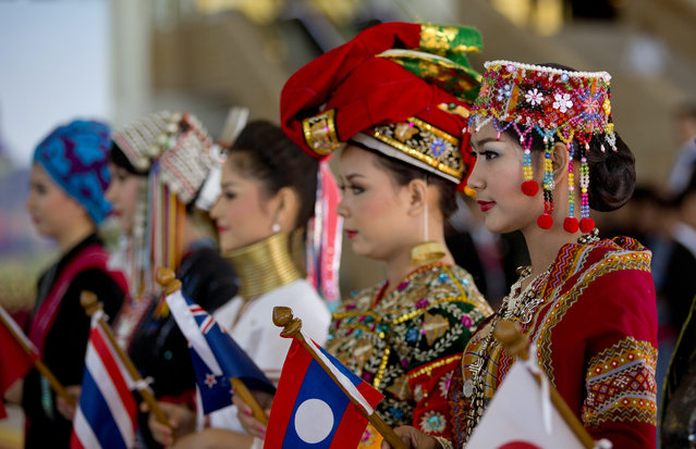 Women in ethnic Chin, Palaung and Padaung attire stand to welcome leaders attending the East Asia Summit at Myanmar International Convention Center in Naypyitaw, Myanmar, Thursday, November 13, 2014. (Photo by Gemunu Amarasinghe/AP Photo)