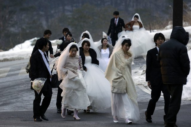 Couples arrive for their mass wedding ceremony at the CheongShim Peace World Center in Gapyeong, South Korea, Sunday, February 17, 2013. Some 3,500 South Korean and foreign couples exchanged or reaffirmed marriage vows in the Unification Church's mass wedding arranged by Hak Ja Han Moon, a wife of the late Rev. Sun Myung Moon, the controversial founder of the Unification Church. (Photo by Lee Jin-man/AP Photo)