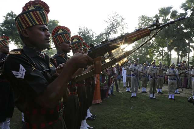 Indian army soldiers prepare to give a gun salute to their colleague Gangadhar Dalai, who was killed in a militant attack in Uri, Kashmir, prior to his cremation in Jamuna Balia village, west of Kolkata, India, Tuesday, September 20, 2016. (Photo by Bikas Das/AP Photo)