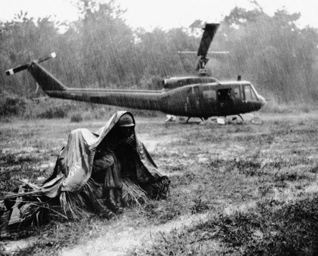 A Vietnamese monsoon downpour drenches men of the U.S. First Infantry Division as an Army helicopter waits for weather to clear so it can take off in a jungle clearing about 50 miles north-northwest of Saigon on November 23, 1965. The helicopter flew into the clearing to resupply troops with C-rations and water. The troops are on search and clear operations in the Viet Cong controlled area. (Photo by AP Photo/SJ)