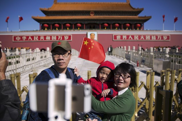 People have their picture taken at the Tiananmen gate as they celebrate National Day marking the 66th anniversary of the founding of the People's Republic of China, in Beijing October 1, 2015. (Photo by Damir Sagolj/Reuters)