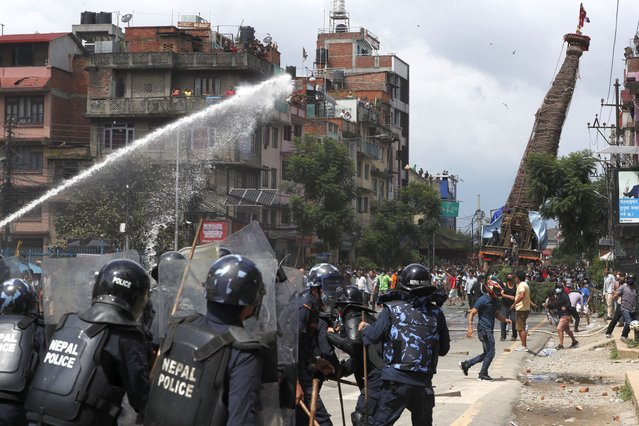 Nepalese protesters defying a government coronavirus lockdown to take part in a religious festival clash with riot police, in Lalitpur, Nepal, Thursday, September 3, 2020. A 5-story-high chariot holding a statue of the deity Rato Machindranath was built but parked for months because of government orders not hold the annual festival due to fear over the spread of the coronavirus. The statue is normally pulled around the city for a month. Police officers in riot gear blocked the protesters when they moved the chariot, dousing them with water cannons. (Photo by Niranjan Shrestha/AP Photo)