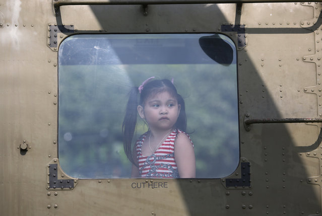 A Filipino girl looks from inside a Philippine Sokol military helicopter during a static display to celebrate the 75th year of the Department of National Defense at Camp Aguinaldo military headquarters in suburban Quezon City, north of Manila, Philippines on Sunday, November 16, 2014. (Photo by Aaron Favila/AP Photo)