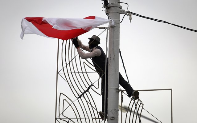 A man in a mask hangs an old Belarusian flag on a light pole during an opposition rally to protest the official presidential election results in Minsk, Belarus, Sunday, September 27, 2020. (Photo by TUT.by via AP Photo)