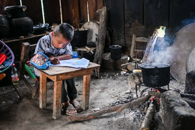 A boy member of the Santiago family, is homeschooled in San Miguel Amoltepec Viejo, Guerrero state, Mexico, on September 8, 2020, amid the COVID-19 coronavirus pandemic. Teachers resist abandoning their students in this impoverished indigenous region of Mexico despite the pandemic. (Photo by Pedro Pardo/AFP Photo)