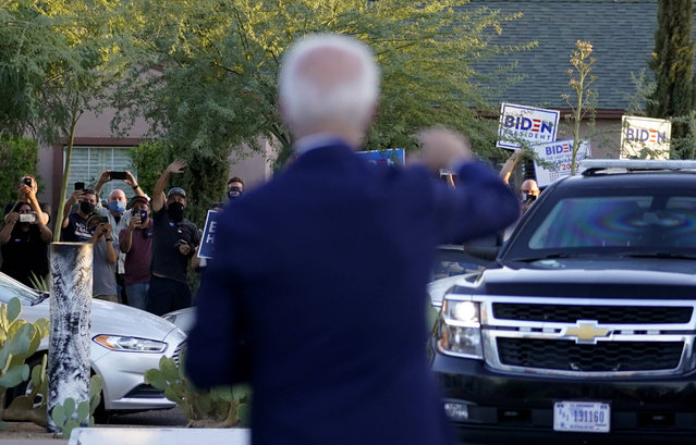 Democratic presidential candidate former Vice President Joe Biden waves to supporters as he and Democratic vice presidential candidate Sen. Kamala Harris, D-Calif., leave Barrio Cafe in Phoenix, Thursday, October 8, 2020, during their small business bus tour. (Photo by Carolyn Kaster/AP Photo)