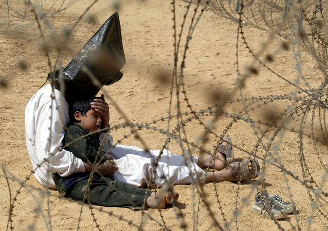 An Iraqi man comforts his 4-year-old son at a regroupment center for POWs of the 101st Airborne Division near An Najaf, Iraq in this March 31, 2003 photo. The man was seized in An Najaf with his son and the U.S. military did not want to separate father and son. (Photo by Jean-Marc Bouju/AP Photo/The Atlantic)