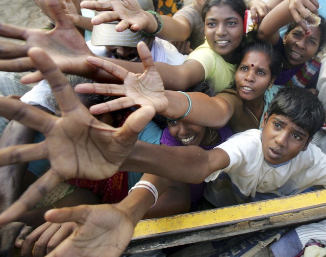 Tsunami survivors rush for clothes and food donated by volunteer organisations in Cuddalore, south of the Indian city of Madras in this December 29, 2004 file photo. (Photo by Arko Datta/Reuters)