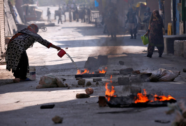 A Kashmiri woman pours water on burning debris after a protest in Srinagar against the recent killings in Kashmir, September 30, 2016. (Photo by Danish Ismail/Reuters)