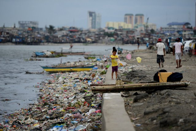 A boy plays next to a seawall in a shanty town at the port area in Manila on December 7, 2014 ahead of the arrival of typhoon hagupit. (Photo by Noel Celis/AFP Photo)
