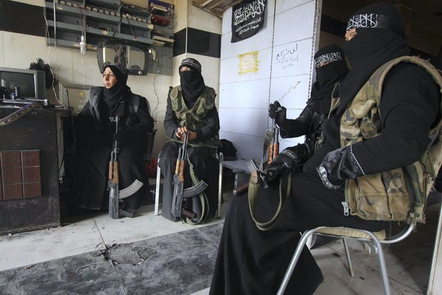 Women members of the Al-Ikhlas (Loyalty) Battalion rest with their weapons in Aleppo March 31, 2013. The Al-Ikhlas (Loyalty) Battalion is a security battalion that involves women that are in charge of erecting sudden checkpoints and raiding houses that contain women in Aleppo. The battalion is under the Ghorabaa (Strangers) Al-Sham Front, controlled by the Free Syrian Army. (Photo by Giath Taha/Reuters)