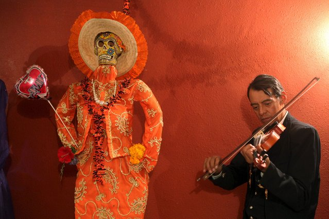 A musician plays his violin next to a depiction of La Santa Muerte (Saint Death) at a shrine during Day of the Dead celebrations in Ciudad Juarez, Mexico, November 2, 2015. (Photo by Jose Luis Gonzalez/Reuters)