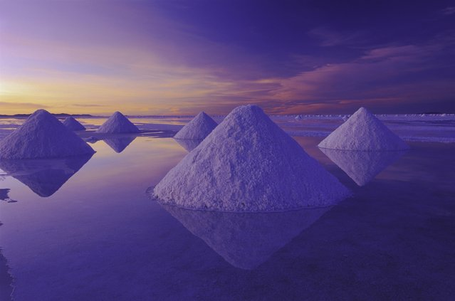 """Pyramids of salt reflect the pink hues of predawn light rising above the Salar de Uyuni in the Altiplano of central Bolivia.  The salt flat is one of the largest in the world and a remnant of an ancient lake"". (Photo by Art Wolfe/Art Wolfe Stock)"