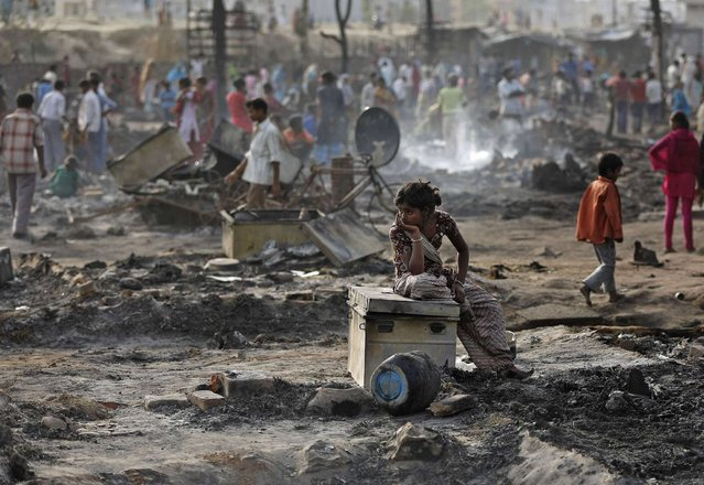 A local resident sits on a trunk amid the burnt debris of her hut after a fire broke out in a slum area in New Delhi April 12, 2013. Two people including a child, died on Friday after a fire broke out in a slum area on the outskirts of Delhi gutting several huts, local media reported. (Photo by Adnan Abidi/Reuters)