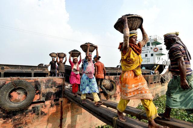 Laborers unload coal from a cargo ship in baskets on their heads at a river bank in Dhaka, Bangladesh on October 15, 2020. Bangladesh reported 1,600 new COVID-19 cases and 15 new deaths on Thursday, bringing the total cases in the country to 384,559 and the total deaths to 5,608, the Directorate General of Health Services (DGHS) said. (Photo by Chine Nouvelle/SIPA Press/Rex Features/Shutterstock)