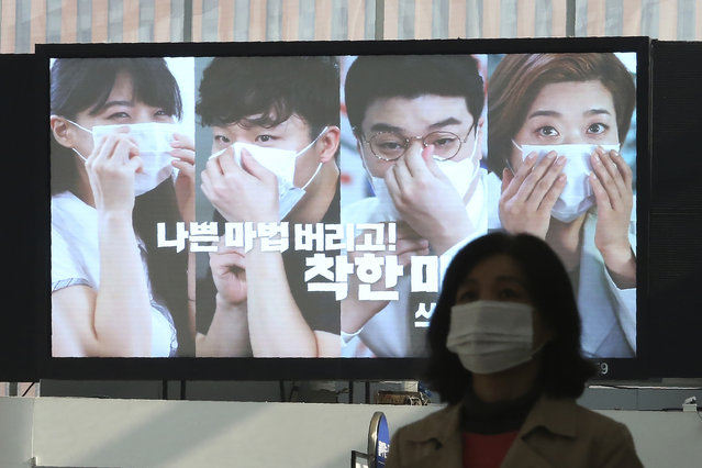 """A screen shows precautions against the coronavirus at the Seoul Railway Station in Seoul, South Korea, Saturday, November 7, 2020. The Korean letters read """"Let's wear a mask in a good way"""". (Photo by Ahn Young-joon/AP Photo)"""