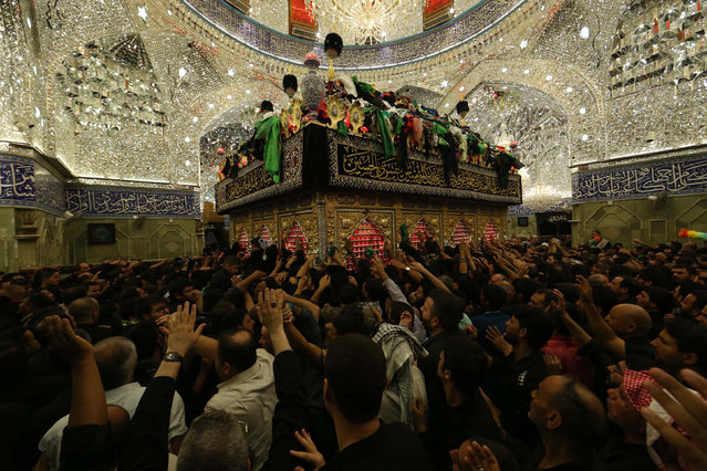 Iraqi Shiites pray inside the Imam Abbas shrine in commemorations on the the eve of the tenth day of the mourning period of Muharram, which marks Ashura, in the holy city of Karbala on October 11, 2016. Ashura mourns the death of Imam Hussein, a grandson of the Prophet Mohammed, who was killed by armies of the Yazid near Karbala in 680 AD. (Photo by Mohammed Sawaf/AFP Photo)