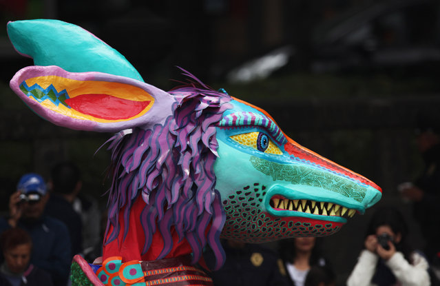 A giant alebrije is paraded through Mexico City, Saturday, December 13, 2014. Alebrijes are colorful statues of all sizes that combine the body parts of different animals to create a new, unique fantasy creature, an art form native to Mexico. (Photo by Marco Ugarte/AP Photo)