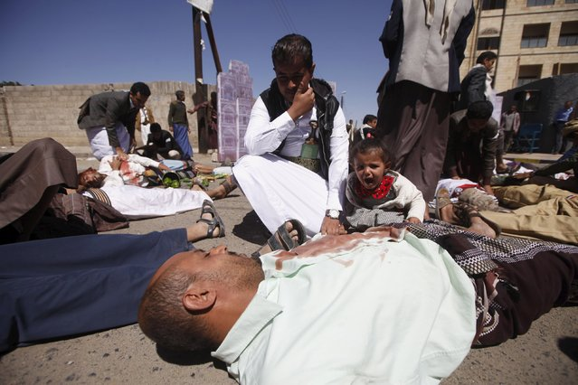 A girl cries while her father lies on the ground with fake blood on his clothes, as he plays the role of an airstrike victim, during a protest against Saudi-led air strikes, in Yemen's capital Sanaa, November 8, 2015. (Photo by Mohamed al-Sayaghi/Reuters)