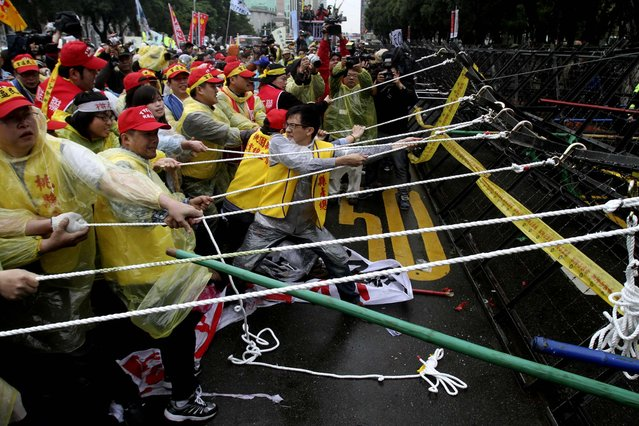 Workers try to pull a road block down during a protest on May Day in Taipei. More than 10,000 Taiwanese workers took to the streets to protest a government reform plan that will cut pension payouts to ease Taiwan's worsening fiscal problems. The protesters said the payout cuts reflect a longstanding government policy to bolster economic growth at the expense of workers' benefits  and compromised workplace safety. (Photo by Chiang Ying-ying/Associated Press)