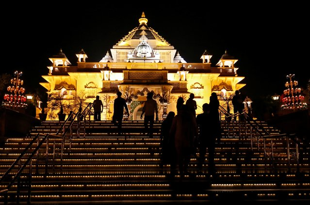 Devotees visit illuminated Akshardham temple on the eve of Diwali, in Gandhinagar, India, November 13, 2020. (Photo by Amit Dave/Reuters)