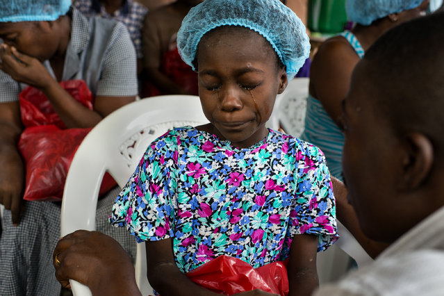 Esther Tokpah, 11 an orphan, weeps as Dr. Jerry Brown tries to console her before she was released from care on Wednesday September 24, 2014 in Monrovia Liberia. Esther, who lost both parents to Ebola was one of two children, among 15, Liberian patients who recovered from Ebola and were released from the ELWA 2 Ebola Treatment Center. (Photo by Michel du Cille/The Washington Post)