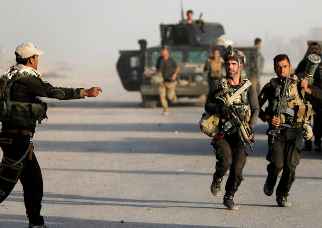 Iraqi special forces soldiers run during clashes in Bartella, east of Mosul, Iraq October 20, 2016. (Photo by Goran Tomasevic/Reuters)