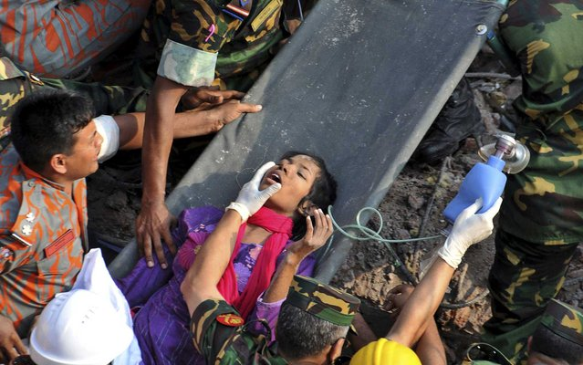 A survivor lies on a stretcher after being pulled out from the rubble of a building that collapsed near Dhaka, Bangladesh, on May 10, 2013. Rescue workers freed the woman buried for 17 days inside the wreckage of a garment factory building that collapsed, killing more than 1,000 people. Soldiers at the site said her name was Reshma and described her as being in remarkably good shape despite her ordeal. (Photo by Associated Press)
