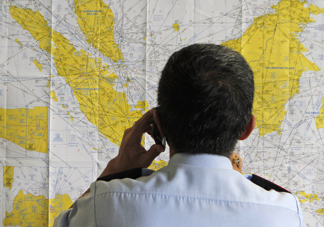 An airport official checks a map of Indonesia at the crisis center set up by local authority for the missing AirAsia flight QZ8501, at Juanda International Airport in Surabaya, East Java, Indonesia, Sunday, Dec. 28, 2014. (Photo by AP Photo/Trisnadi)