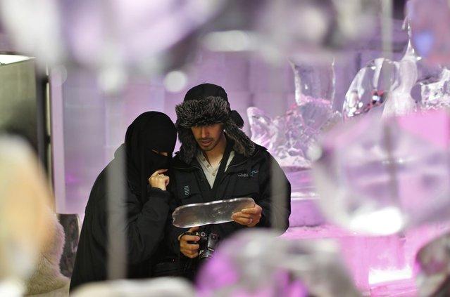 A Saudi Arabian couple inspect the menu at Chillout cafe in Dubai May 12, 2013. (Photo by Ahmed Jadallah/Reuters)