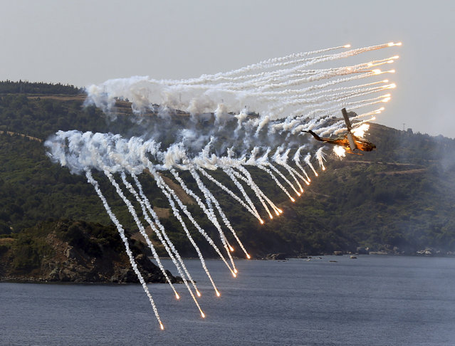 A Turkish army helicopter in action after an amphibious landing during EFES 2018 drills in Seferihisar in Aegean Sea near Izmir, Turkey, Thursday, May 10, 2018. Turkey shows off its military hardware in the EFES 2018 drill. (Photo by Emre Tazegul/AP Photo)