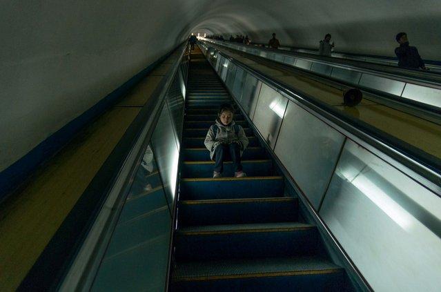 A girl sits on the escalator at the Pyongyang metro, Feburary 2012. (Eric Testroete)