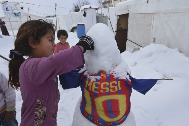 A Syrian girl makes a snowman outside her tent at a refugee camp in al-Majdal village, Bekaa valley, east Lebanon, Thursday, January 8, 2015. Snow fell in the Middle East as a powerful winter storm swept through the region, killing at least two Syrian refugees in Lebanon and forcing thousands of others who have fled their country civil war to huddle for warmth in refugee camps. (Photo by Hussein Malla/AP Photo)