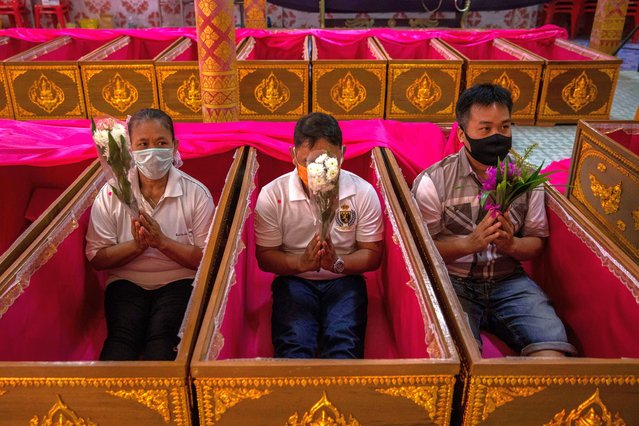 "Thai devotees lay down in coffins during a resurrection ceremony at Wat Takien in hopes of cleansing themselves of bad karma upon their ""rebirth"" on December 31, 2020 in Bangkok, Thailand. Thai temple goers take part in a traditional resurrection ceremony on New Years Eve at Wat Takien, located in Nonthaburi province, 20 kilometers north of Bangkok, Thailand. The temple is famous for its resurrection ceremonies where Thai's ritualistically die before being reborn. During the ritual, Thai worshippers tie a white thread around their heads and take part in a group prayer before lowering themselves into coffins where Thai monks perform the resurrection ceremony. The belief is that the resurrected worshipper is cleansed of their bad karma and will be blessed with good fortune and health in the new year.  Due to the recent spike in COVID-19 cases in Thailand, the temple has implemented strict mask wearing and social distancing measures. (Photo by Lauren DeCicca/Getty Images)"