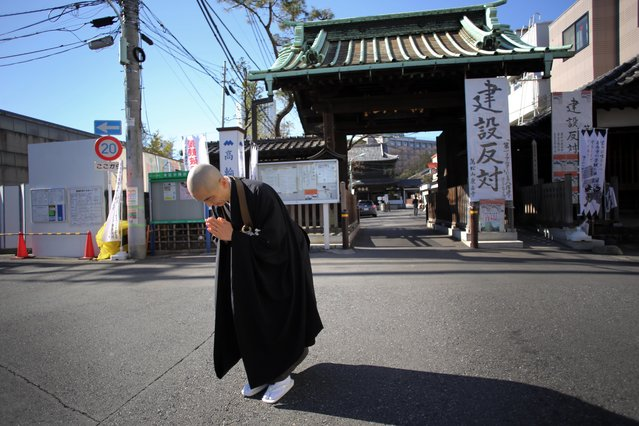 In this January 8, 2015 photo, a monk Kenmyo Muta bows at the condominium construction site and the gate of Sengakuji temple in Tokyo. (Photo by Eugene Hoshiko/AP Photo)