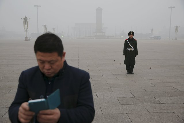 A man checks his phone in front of a paramilitary soldier at the Tiananmen Square on an extremely polluted day as hazardous, choking smog continues to blanket Beijing, China December 1, 2015. (Photo by Damir Sagolj/Reuters)