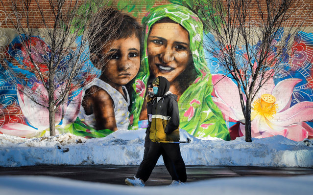 A couple wearing masks walk past a mural of a mother and child in Calgary, Alta., Monday, December 28, 2020, amid a worldwide COVID-19 pandemic. (Photo by Canadian Press/Rex Features/Shutterstock)
