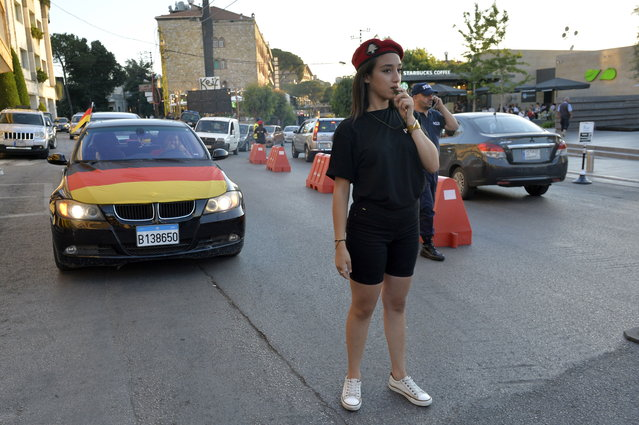 A Lebanese university student wearing municipality police costume regulates the traffic in the village of Brummana, east Beirut, Lebanon, 23 June 2018 (issued 24 June 2018). The touristic town of Brummana is making a daring move in anticipation of the crowded summer season, by forming a group of young policewomen wearing mini shorts to regulate the traffic. This move raised controversy especially over the Lebanese social media in a debate whether those female young adults are being used and mistreated via their special casual uniform in comparison to their male coworkers, or they are serving their purpose of attracting more curious tourists while doing their job. (Photo by Wael Hamzeh/EPA/EFE)