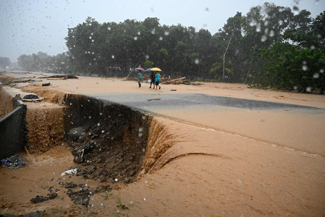 Men walk along a flooded road after the River Chirichil overflowed following heavy rains caused during the passage of Hurricane Eta in Toyos, Honduras on November 4, 2020. Hurricane Eta slowed to tropical storm speeds on Wednesday morning even as it pummeled Nicaragua, killing two people there and one in neighboring Honduras, while unleashing fierce winds and heavy downpours. (Photo by Orlando Sierra/AFP Photo)