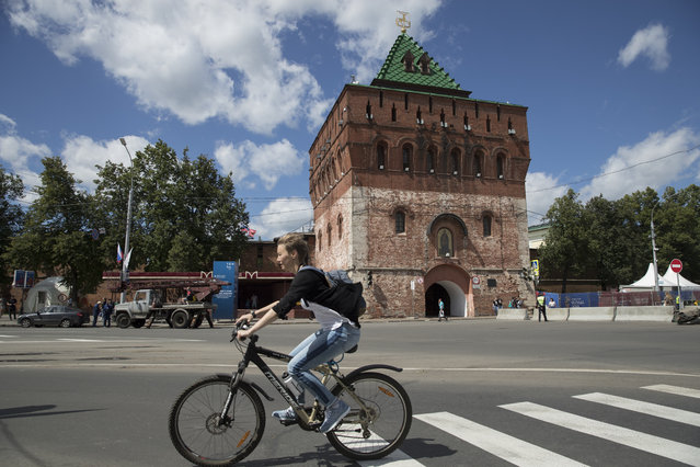 In this Wednesday, June 20, 2018 filer, a woman rides a bicycle next to the Kremlin's wall in Nizhny Novgorod, Russia. (Photo by Pavel Golovkin/AP Photo)