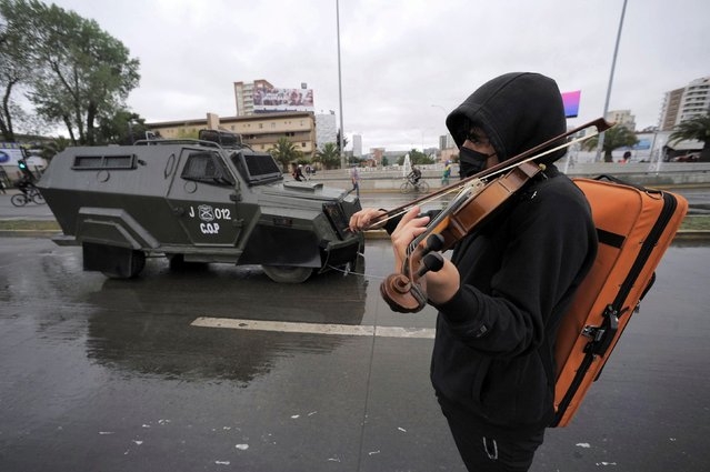 A man plays a violin during a protest after a police officer shot dead a street performer in the southern area of Panguipulli, in Concepcion, Chile, February 6, 2021. (Photo by Jose LuÌs Saavedra/Reuters)
