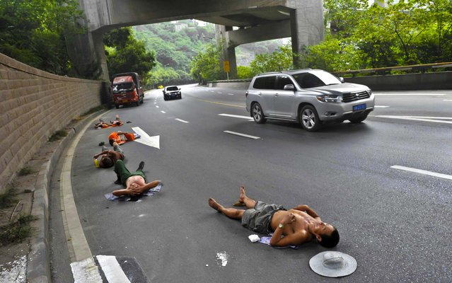 Laborers who work nearby nap on a road as cars drive past in Chongqing Municipality, China, on July 23, 2013. (Photo by Reuters)